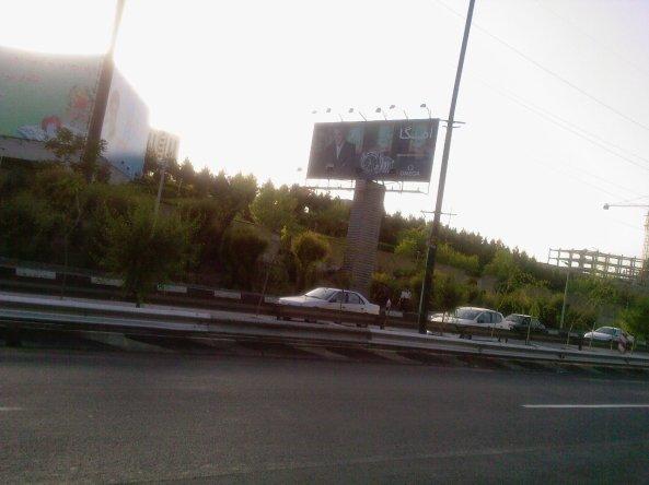 عکس وی برای تبلیغ یک مارک ساعت گرانقیمت بر روی یک تابلوی تبلیغاتی در تهران