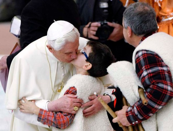 Pope Benedict XVI kisses a young bagpipe player at the end of his weekly audience in the Paul VI hall at the Vatican